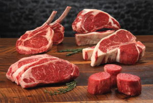 Certified Angus Beef® brand Prime Raw Middle Meat Cuts - Prime Raw-Middlemeat Variety, Standing Bone-in Ribeyes, Boneless ribeye, Porterhouses, Strip Steaks and Tenderloin Filets with herb sprigs on classic wood